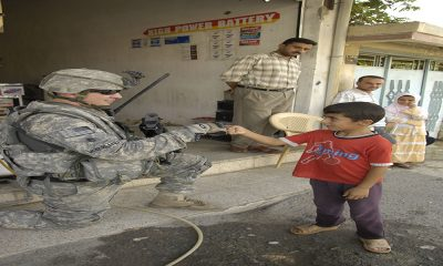 U.S. Army Staff Sgt. Aaron McFarland, from 1st Battalion, 8th Infantry Regiment, bumps knuckles with an Iraqi boy while he provides security during a market assessment at the Cherry Market in Al Karama, Mosul, Iraq on Sep. 17, 2008. (U.S. Army photo by Pfc. Sarah De Boise/Released)