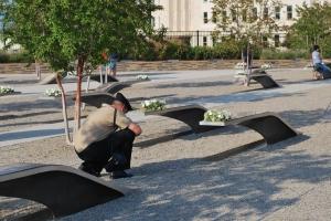 An American service member kneels at the Pentagon Memorial