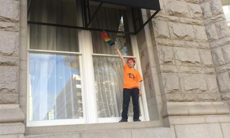 BCC student Marxe Orbach climbs onto a Trump Hotel window and waves a rainbow flag, as a crowd of protesters watches. Photo by Yael Hanadari-Levy.