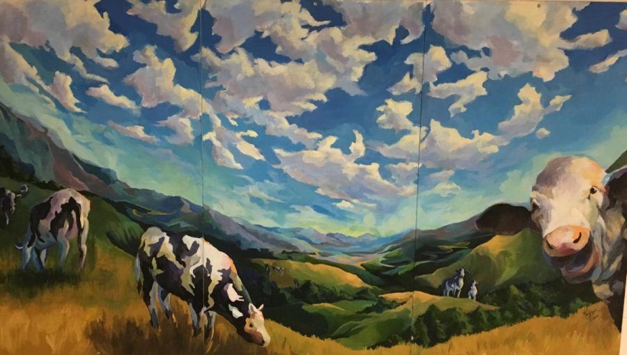This mural of cows grazing in a field is hangs near the gym on the main level of the school. This piece of art is one of the many that students question the origin. Photo by Jessica Silverman