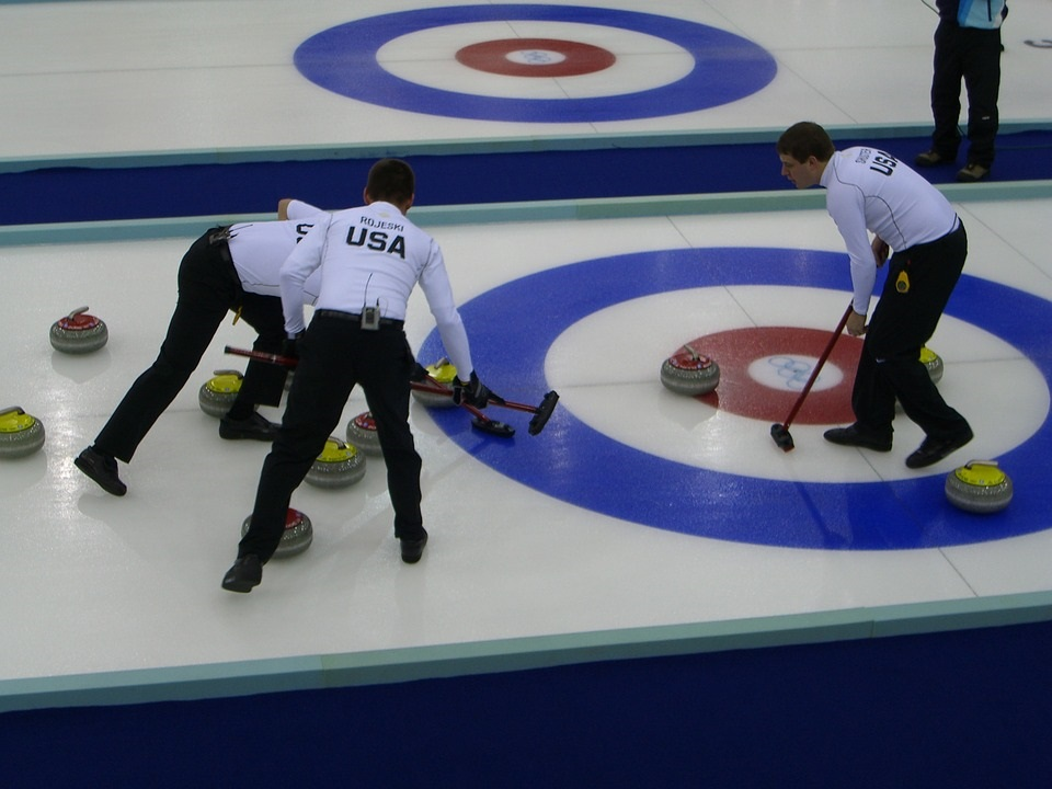 The US curling team sweeps a curling stone.  The US team certainly has nothing on the new WJ curling team, coming next year.  Photo courtesy of pixabay images.