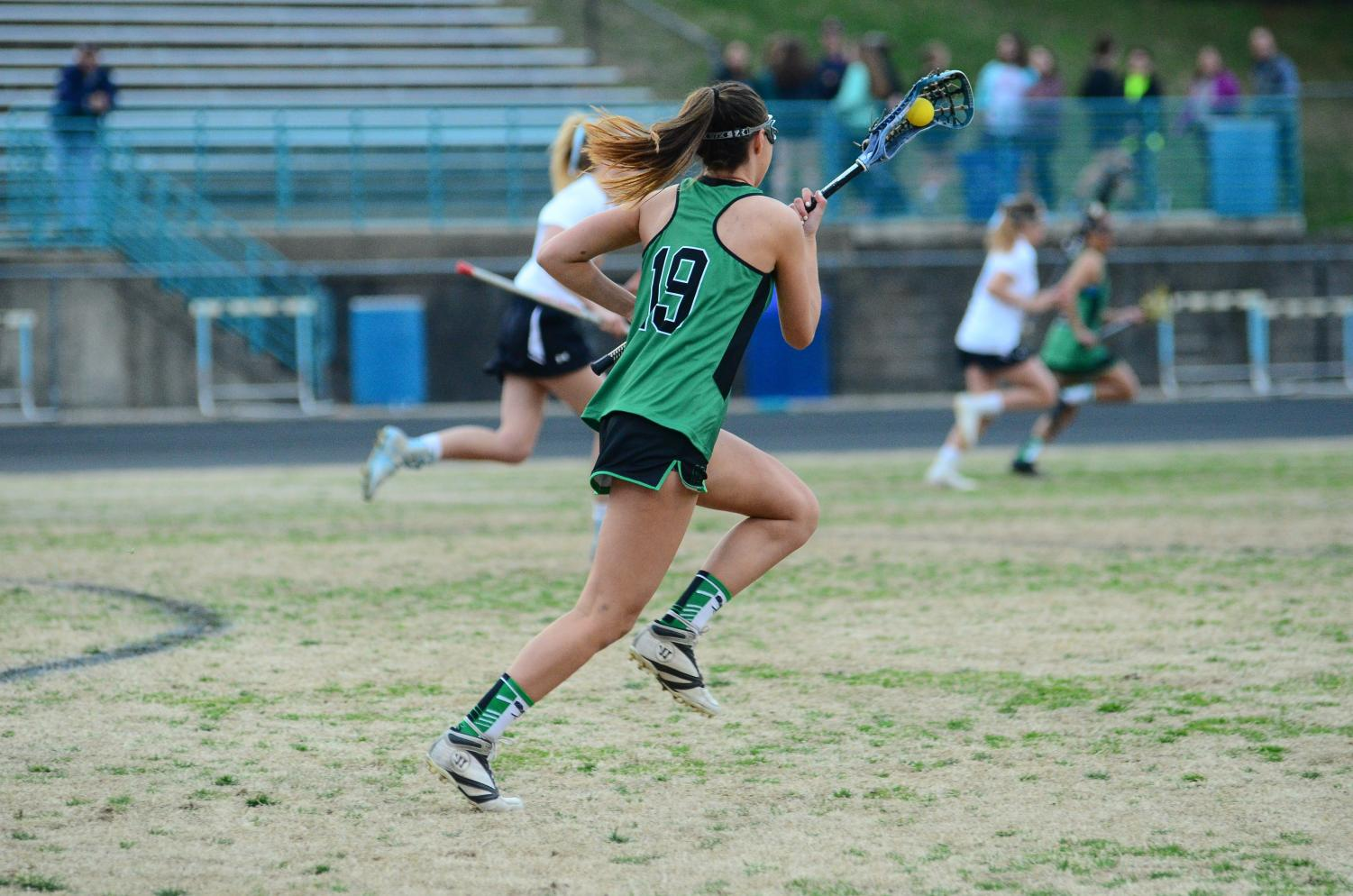 Senior captain Ashley Smith runs down the field, looking to go on the offensive. Girls lacrosse is off to a great start in the playoffs, winning both games so far against Einstein and Churchill.