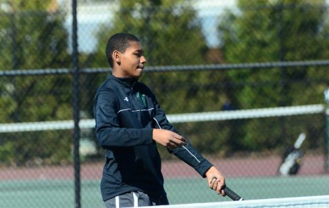 Junior Ian Greenwood hits a volley at the net. Boys' tennis finished their regular season with an 8-4 record.