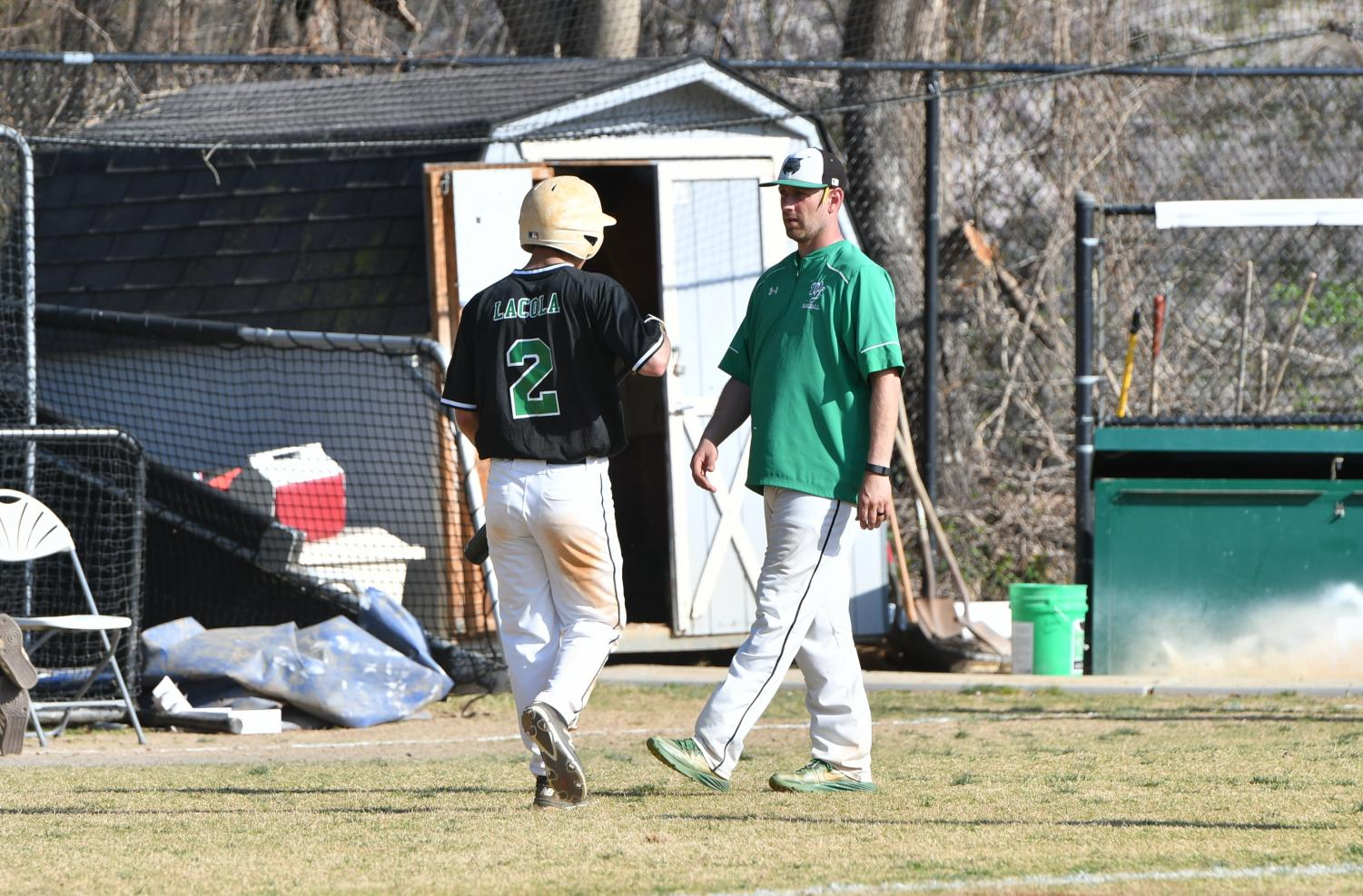 Junior outfielder Anthony Lacola converses with coach Steve Sutherland. WJ had a tough loss against Whitman in the first round 19-16. Courtesty of Lifetouch.