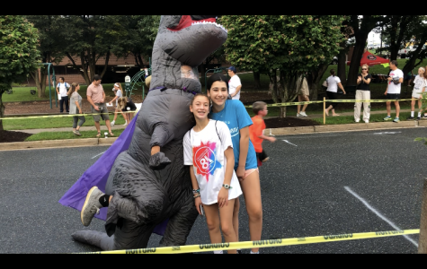 Middle school students Ila Gordon and Pearl Hoffman- Byer pose with one of the mascots of a sponser. Children and families wait at the finish line for their relatives and friends to finish the race.