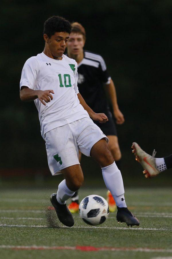 Senior midfielder Kamyab Salehi-Pirouz avoids the defender while turf pellets fly around his feet. Health concerns regarding the artificial turf have caused debate over its use on school fields.