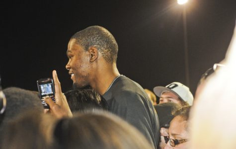 NBA star Kevin Durant on his phone during a basketball fundraiser.