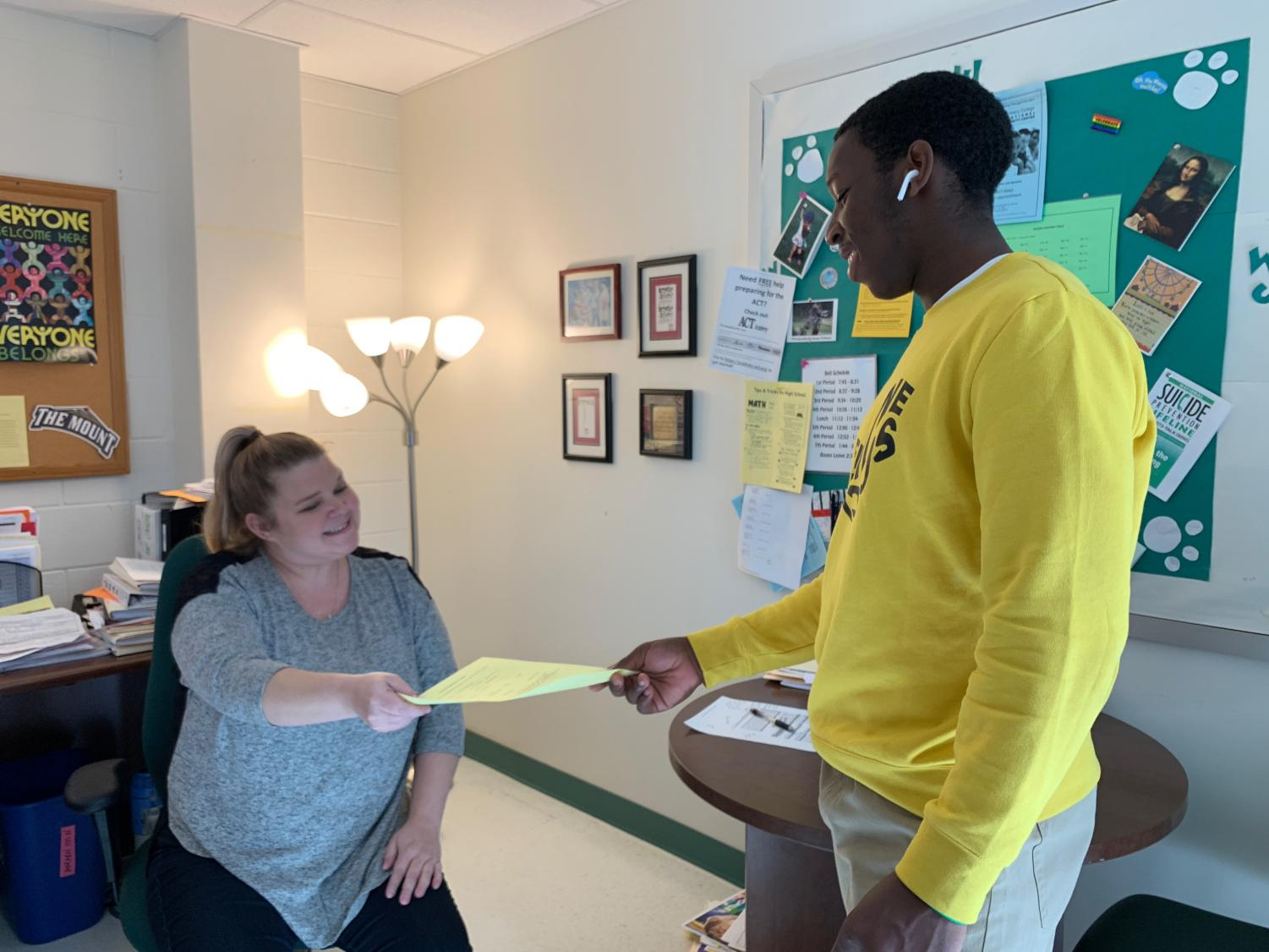 Senior DH Chris Manguelle hands a student transfer form to counselor Jamie Ahearn. Counselors try to help students new to WJ, but MCPS policy can make this difficult.