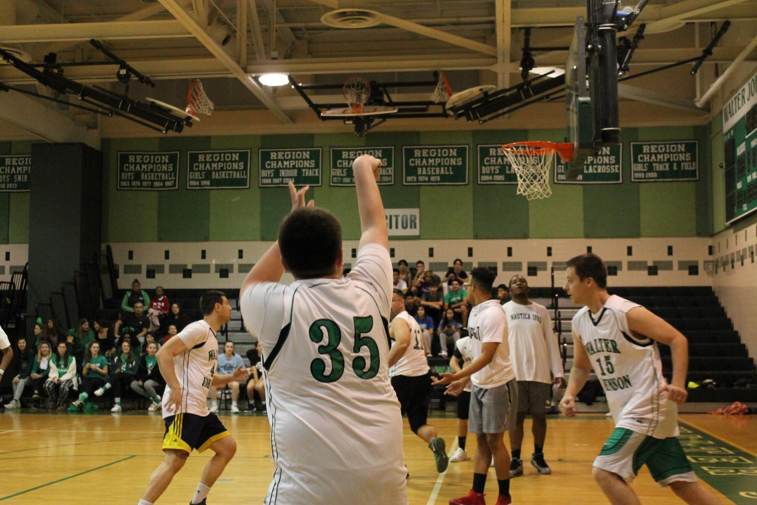 A teacher plays in the student/staff basketball game. The staff won the game by two points.