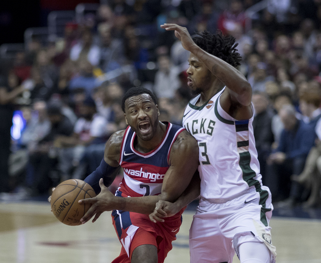 Wall (left) with the Wizards in 2018. The five time all-star drives into the lane for the layup.