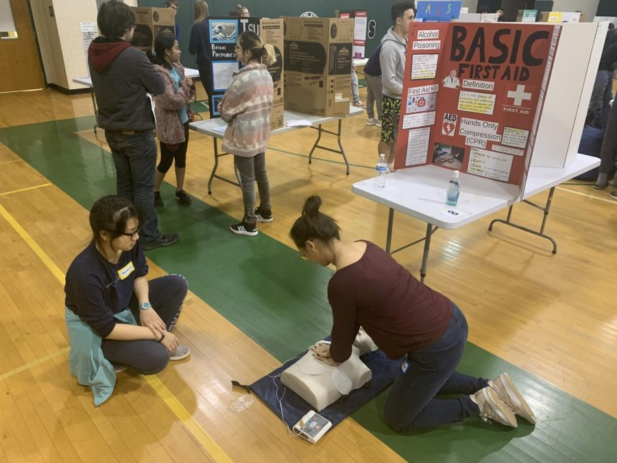 Two+students+practice+their+CPR+skills+to+demonstrate+the+importance+of+basic+first-aid+knowledge.+This+was+one+of+many+interactive+presentations+at+the+fair+that+taught+students+certain+health+skills.+