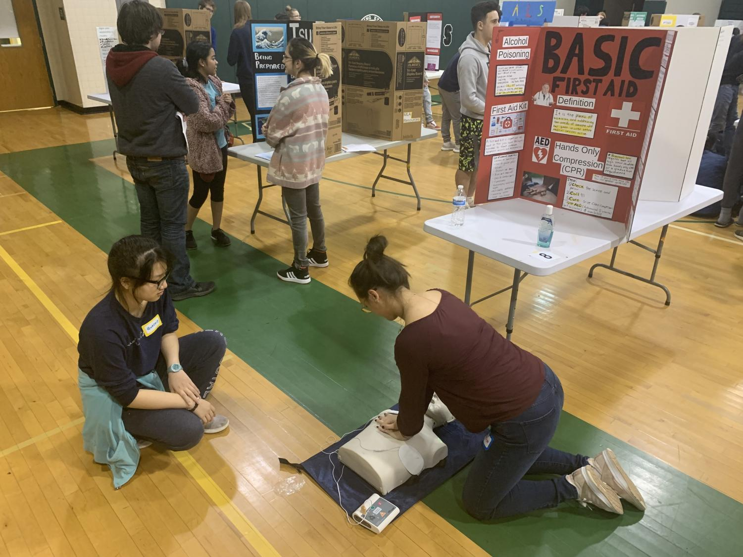 Two students practice their CPR skills to demonstrate the importance of basic first-aid knowledge. This was one of many interactive presentations at the fair that taught students certain health skills.