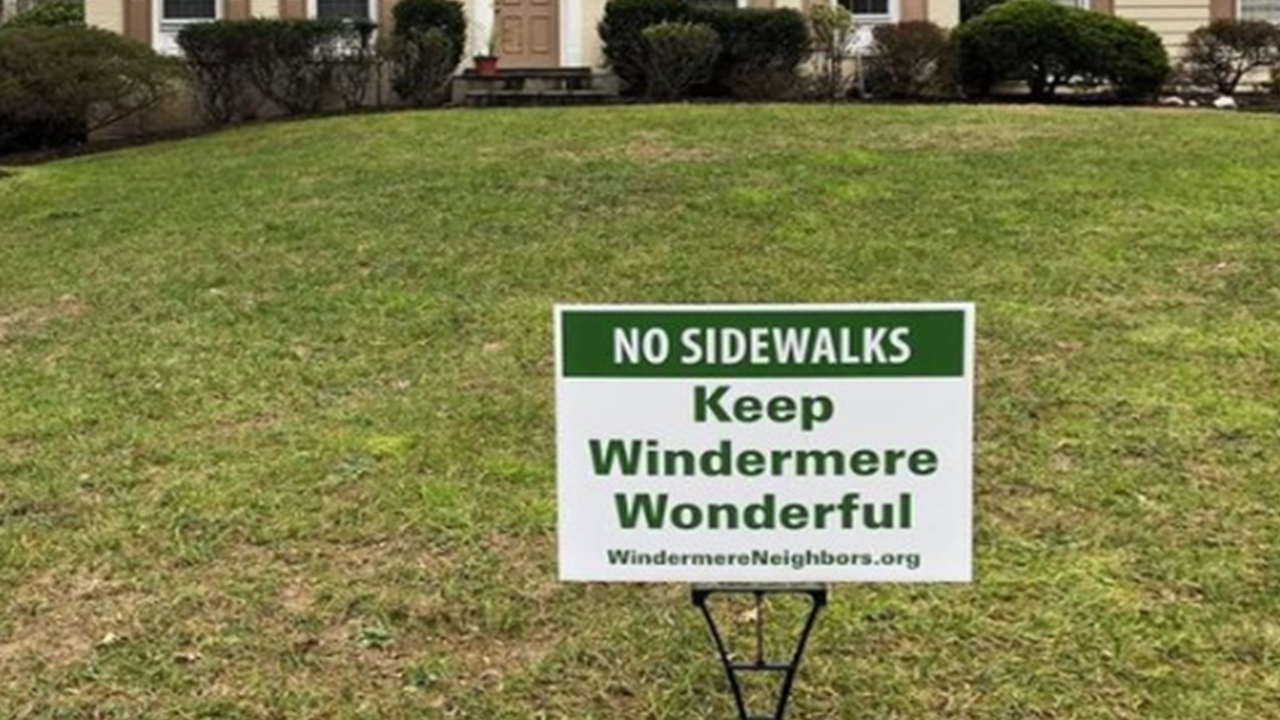Nearly 70 mature trees will need to be cut down in Windermere alone to make way for sidewalk construction, which will only be on one side of the street. Residents are concerned about property value, the environmental impact, and the changing appearance of the neighborhood they call home. This photo shows a lawn poster that is now a common sight throughout the Windermere and Luxmanor neighborhoods.