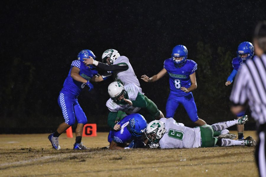 Senior Aidan Williams dives for a loose ball as a small fight emerges in the WJ-Churchill football game last November. WJ's rivalry with Churchill extends beyond the athletic setting, as students from each school plagiarized the other school's stadiums.