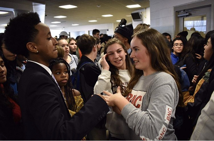 Junior Nate Tinbite talks to a Watkins Mill High School student as she congratulates him on becoming one of the final two candidates for SMOB. The hallways were filled with students excited about Tinbite's campaign in the final stretch before voting on April 24.