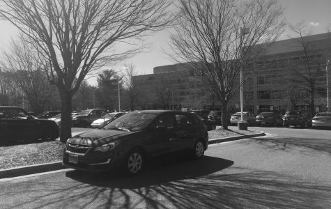 A student parks their car outside of a parking space. Due to the overwhelming amount of juniors who need parking spaces without  parking passes, students have resorted to alternative spaces.