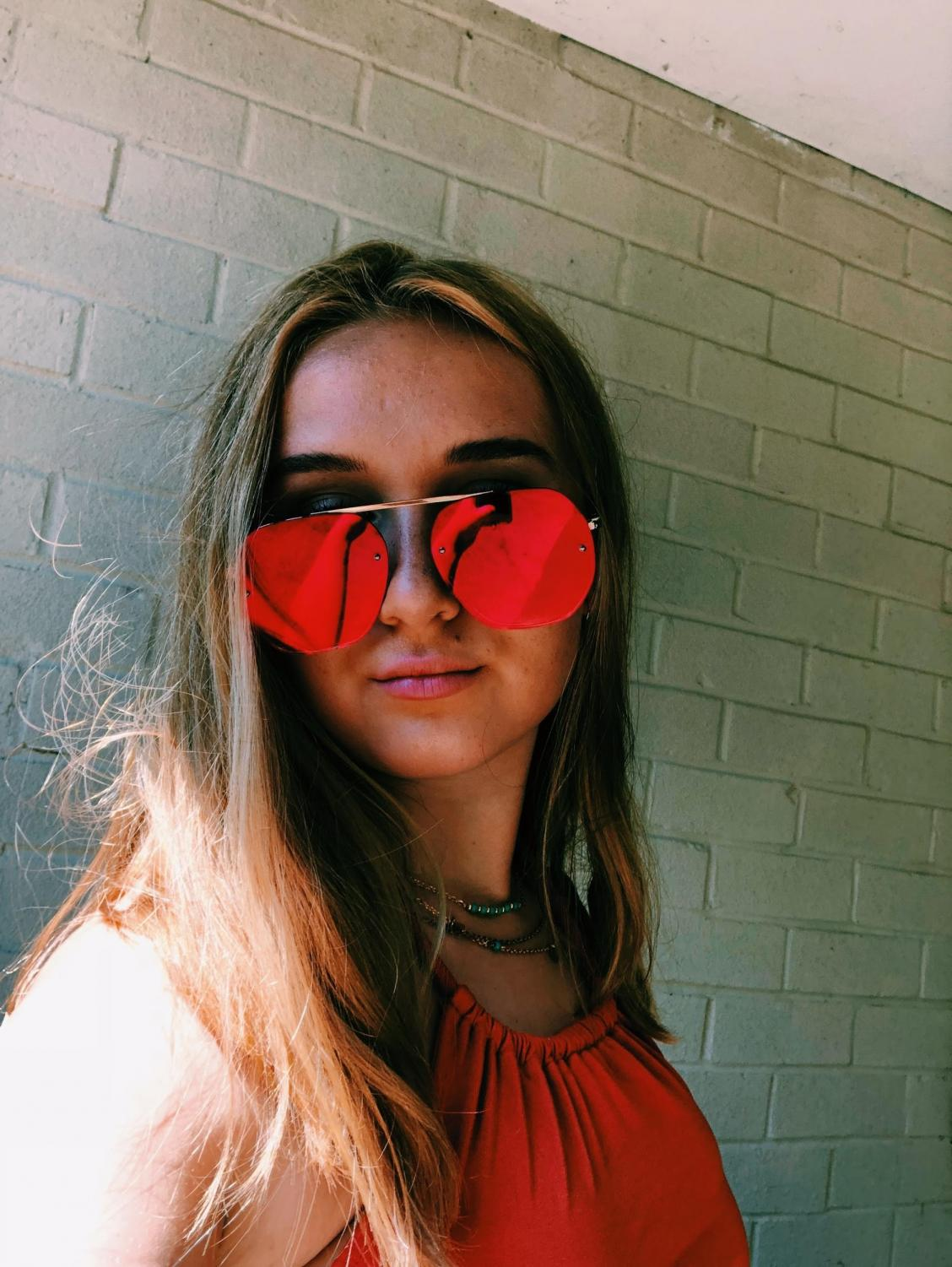 Junior Holly Darby tops off her outfit with a bold pair of red sunglasses. Photo courtesy of Holly Darby