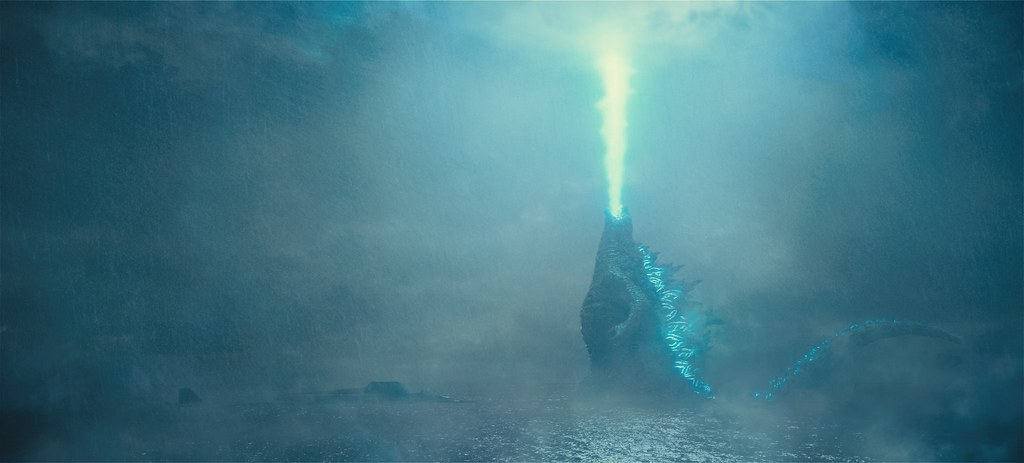 Godzilla emerging from the waves and breathing his iconic atomic breath.