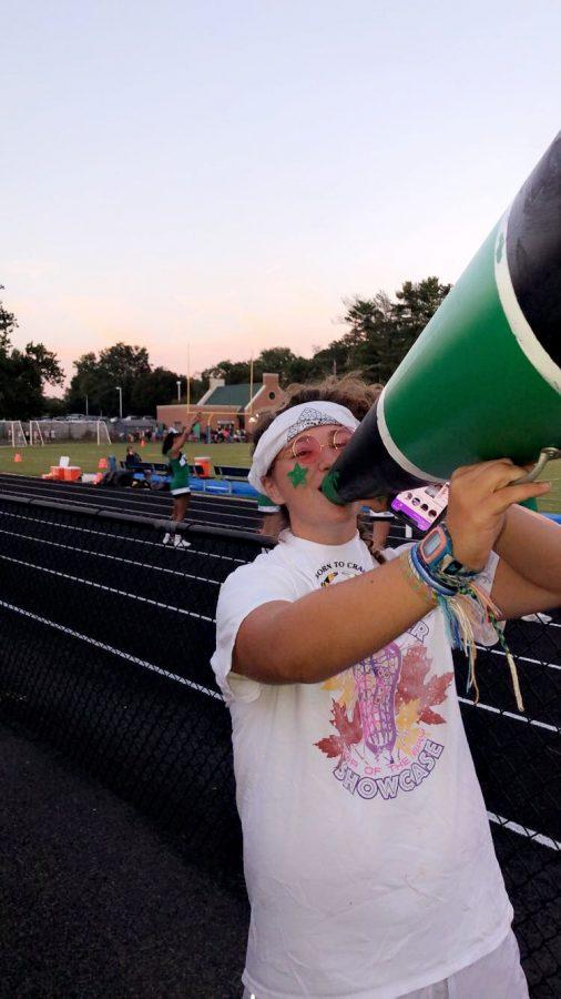 Senior class president Colleen Besche encourages freshman to participate in school spirit at football games.