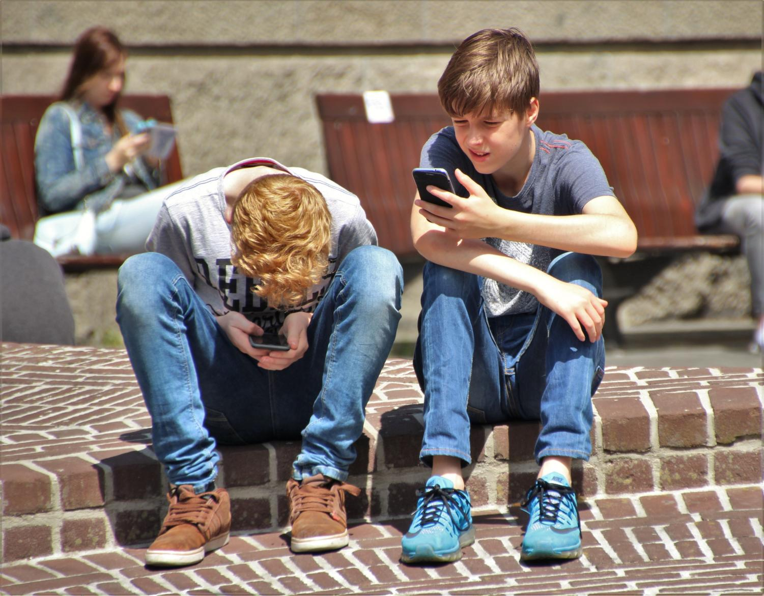 Two young boys sit adjacent to one another yet are not socializing. Given that the average age of cell phone users is so young nowadays, this sight is not a rarity.