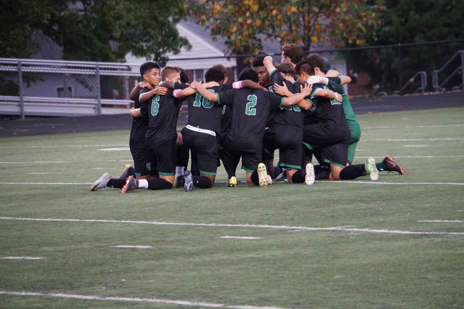 Boys varsity soccer huddles up pregame. They look to get to the old heights set by the 2016 state championship team.
