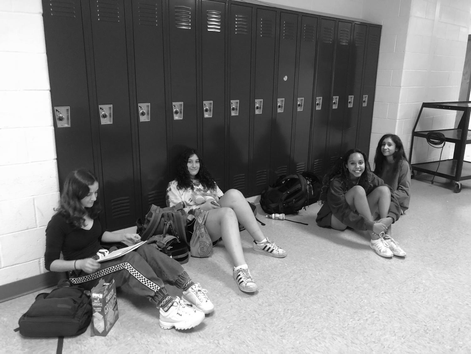 Junior Christine Vassel, freshman Sarah Lawerence, sophomores Jessica Vincent and Valeria Guillen talk and work on homework while waiting to get into their team room before practice.