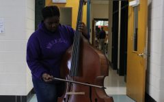 Semira Hill playing a bass outside the band practice room. Hill can play over half a dozen instruments ranging from the drums to the violin, and she is also a part of Madrigals, the highest level choir class WJ offers.