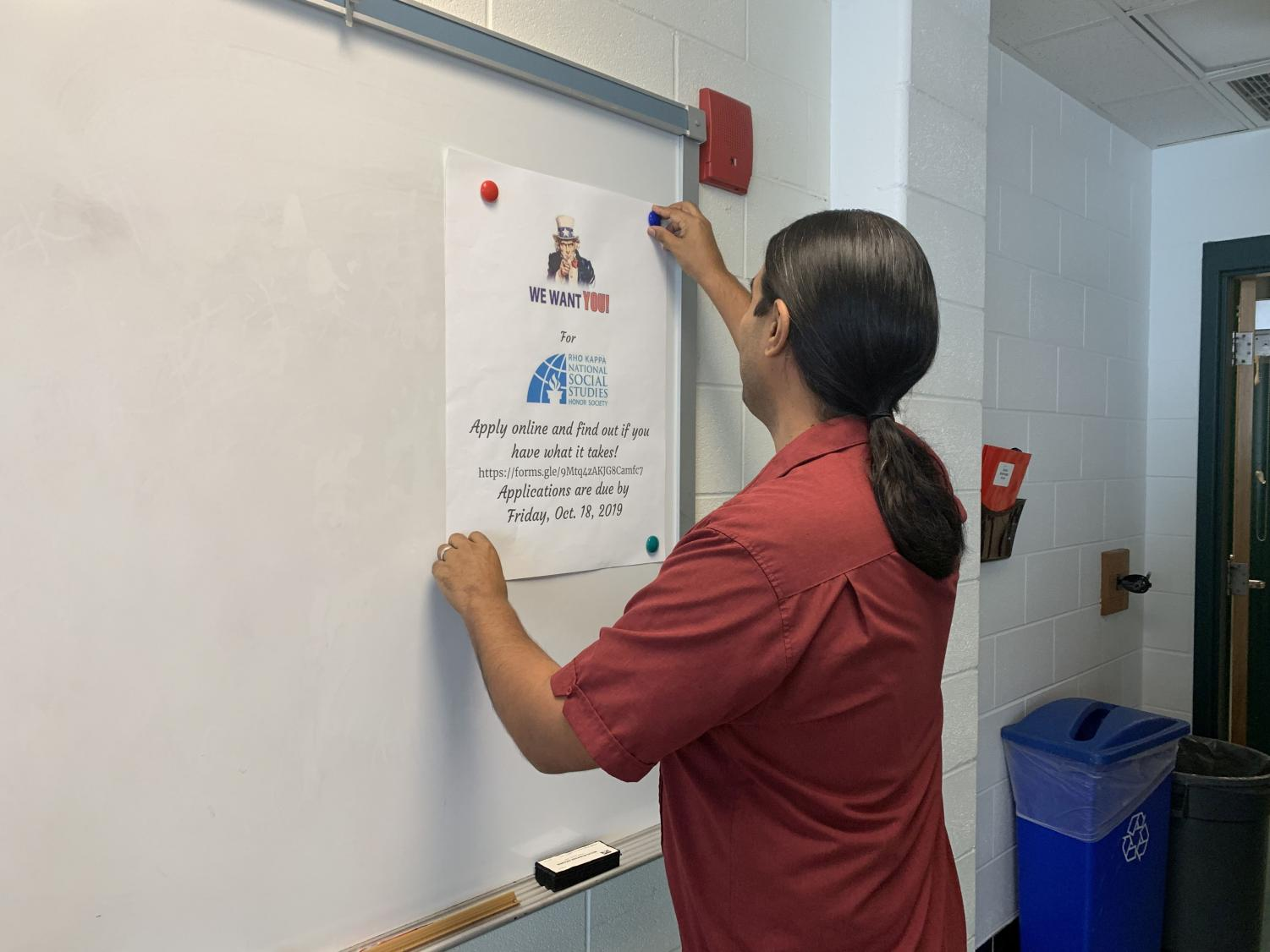 Social Studies teacher Oscar Ramos hangs a poster in his room. Given that it is his first year, decorating the walls makes him feel more settled in.