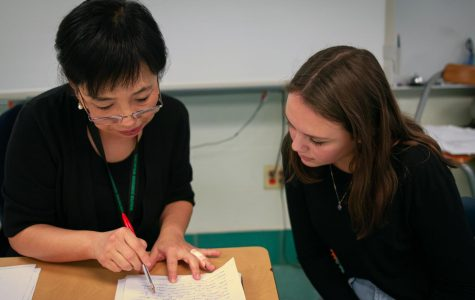 Xuhua Lucia Liang assists a student with their work during lunch. Students often come to Liang's classroom when they need help on a topic in Spanish.
