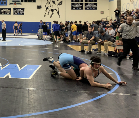 Junior Joseph Meyer gets pinned to the floor by an opposing school's wrestler. WJ faced off against schools outside of MCPS at a tournament in Bel Air, MD.