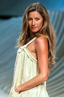 Supermodel Gisele Bundchen naturally poses on the runway. Her minimal look and windy hair show the power of natural beauty. This contrasts with the 2019 bratz doll-makeup trends.
