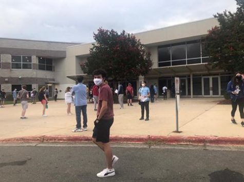 "Senior Alex Finch stands outside of the SAT testing center in Durham, North Carolina. After observing the socially-distanced lines, face-covering masks, and diligent temperature checks, Finch described the setting as ""dystopian"""