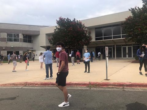 Senior Alex Finch stands outside of the SAT testing center in Durham, North Carolina. After observing the socially-distanced lines, face-covering masks, and diligent temperature checks, Finch described the setting as