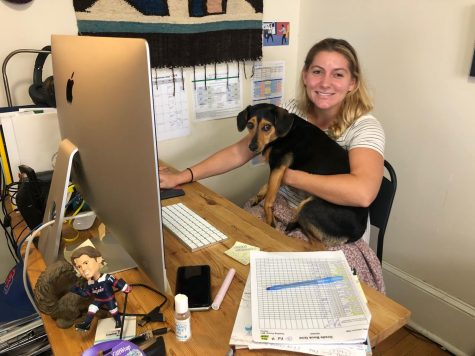 "Psychology teacher Melanie Schwed poses with her puppy at her virtual ""classroom."" Although her teaching is still quite similar to when it was in person, she misses being able to socially interact with students and co-workers."