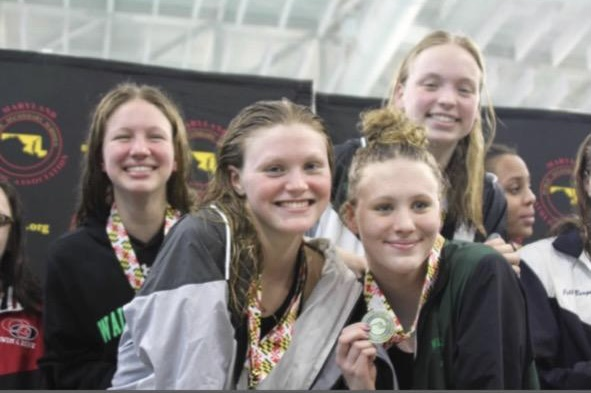 Senior swimmer Jane Umhofer takes a picture with her teammates as they wear medals together.