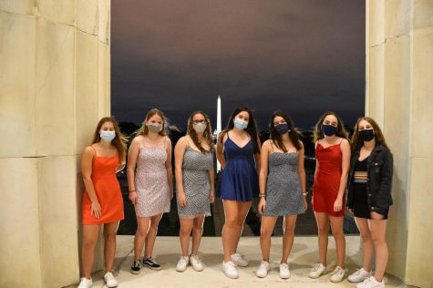 (Left to right) Seniors Nicole Uhl, Anne-Fleur Winter, Danielle Nevett, Ella Mochizuki, Sophie Kotlove, Emmie Maisel and Maggie Lieberman pose for a photo in their dresses and masks at the Lincoln Memorial.