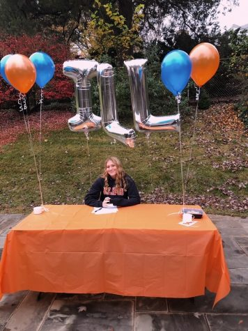 "Lights, camera, action! Senior Jane Umhofer smiles as her picture is taken. She committed to the University of Illinois to continue her swimming passion. ""I am super excited to join a great group of ladies,"" Umhofer said."