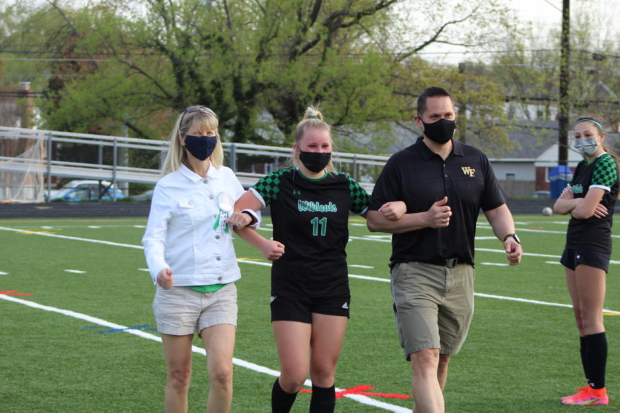 In typical senior night fashion, senior Courtney Schneider and her parents walk to greet the coaching staff and Principal Jennifer Baker.