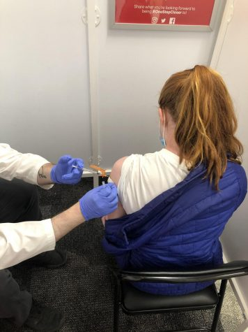 Junior Caroline Stewart gets her shot covid vaccine. Most students, ages 16 and up, have taken initiative to get vaccinated while younger students are just now able to get the vaccine.