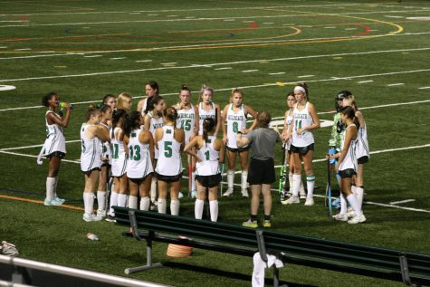 Coach Hannah Teicher plots a course-of-action with the entire field hockey team during half time. The team listened with the hopes of growing their lead.