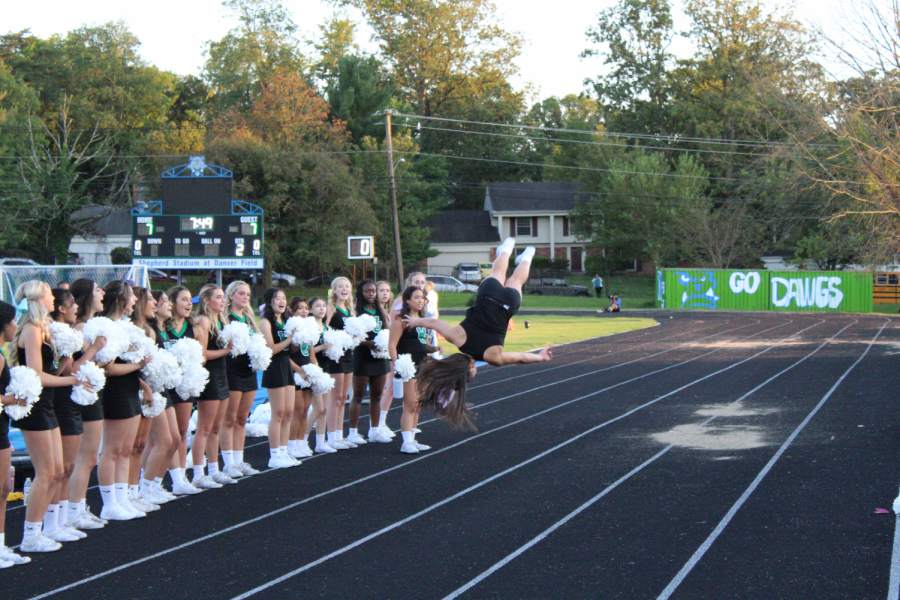 Sophomore Kimberly Shian does a flip during one cheers routines. The squad cheered on the WJ team throughout the whole game, always keeping spirits up.
