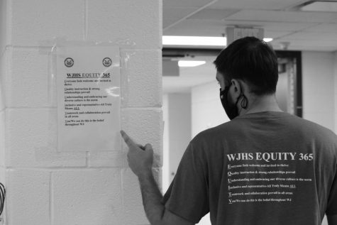 Counselor James Stradley wears his Equity 365 shirt and points to an Equity 365 sign. Signs were posted throughout hallways to remind students and staff to follow the initiatives steps.