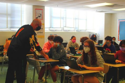 """English teacher Marc Waldman assists a student with an English assignment on his Chromebook. Waldman encourages questions and participation in the classroom. """"I just hope that people always realize that they can approach me, and if I can't help them, I guarantee you, I know someone who can,"""" Waldman said."""