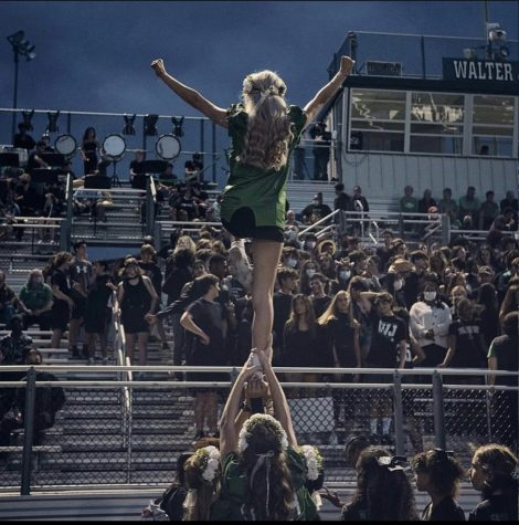 Junior Ava Franke pumps up the crowd during our homecoming game. Franke is a flyer for the team, striking a posed lib with one leg in the air.
